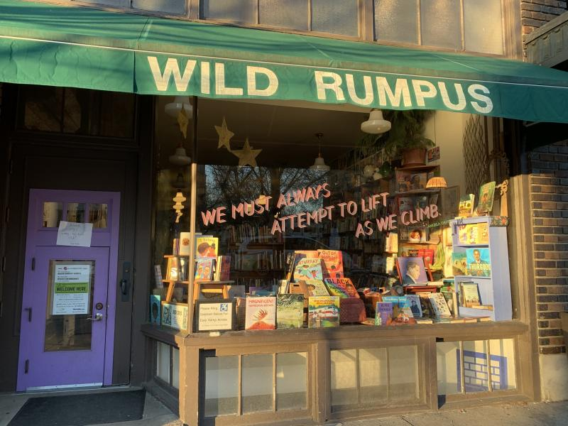 "Wild Rumpus storefront with green awning and a quote from Angela Davis: ""We must always attempt to lift as we climb."""